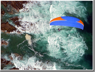Leo Andrade flying his tandem paraglider over Iquique's coast toward Cavancha beach, Iquique, Atacama Desert, Chile