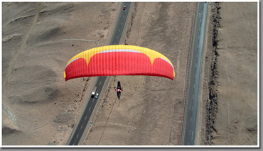 Jarek Wieczorek racing cars in his paraglider, Iquique, The Atacama Desert, Chile