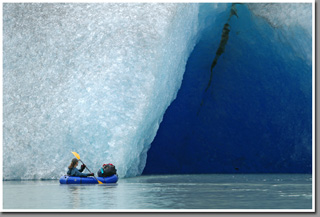 KSZ paddling her packraft into an ice cave created by melting ice of Glacier Steffen - Southernmost glacier of Northern Patagonian Ice Field, Aisen, Patagonia, Chile
