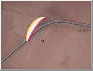 Tandem paraglider piloted by Philip Maltry with his daughter over Patillos take-off, Iquique, The Atacama Desert, Chile