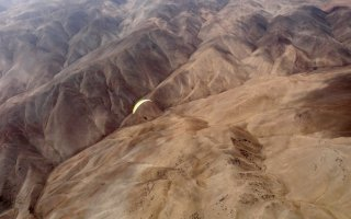Winter is over - Carlos Curi flying his paraglider over a desert plateau near Iquique, The Atacama Desert, Chile