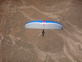 San Chango - A pilot flying his competition paraglider MacPara Magus 6 from the new XC takeoff Chango, The Atacama Desert, Chile
