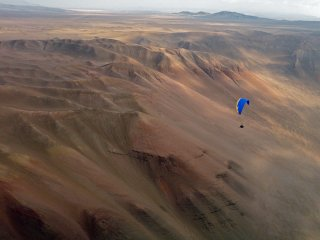 "Evening soaring - Bob Janzen from USA flying over high wind mountain desert area called ""cementario dos"" during one of evening XC flights, Iquique, The Atacama Desert, Chile"